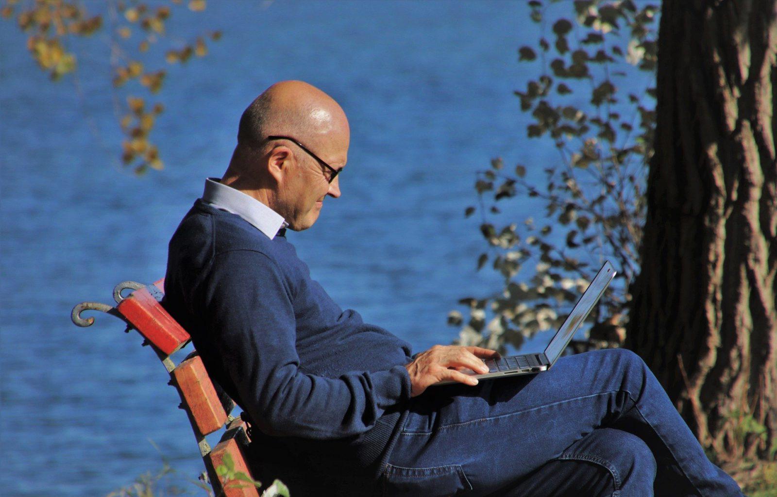Elderly Man sitting on a bench beside the sea
