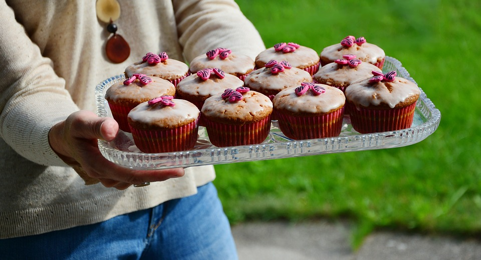 Woman Holding Cup Cakes on a Tray