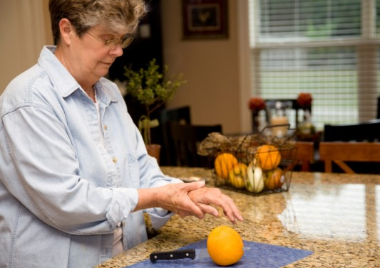 Woman in kitchen with painfull hands